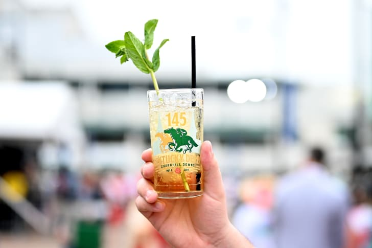 A photo of a person holding a mint julep at the Kentucky Derby