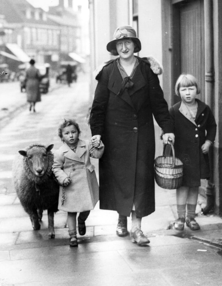 A mother walks her two children, one of whom is walking a sheep