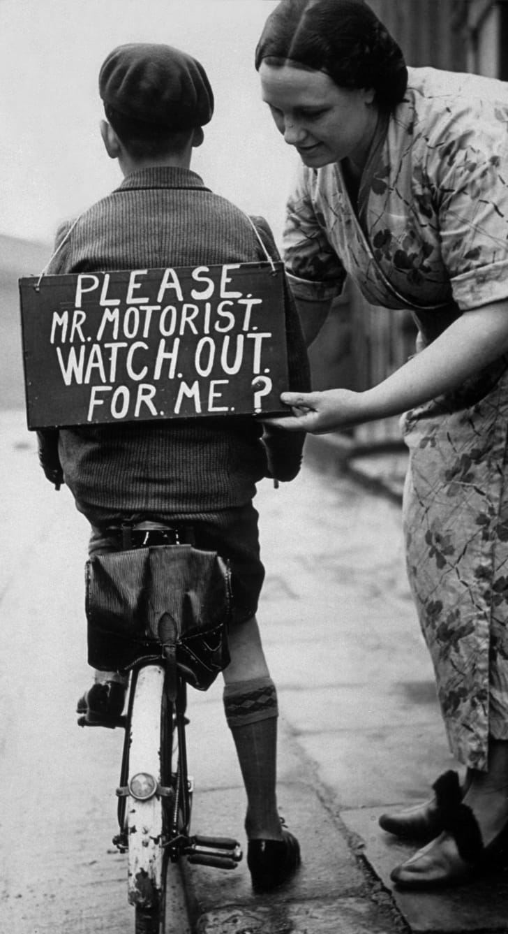1937: A mother fastening a notice reading 'Please Mr Motorist, watch out for me', onto her son's back before he sets out on a trial bicycle ride