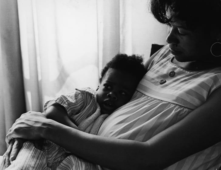 Portrait of a mother sitting with her young girl, circa 1970