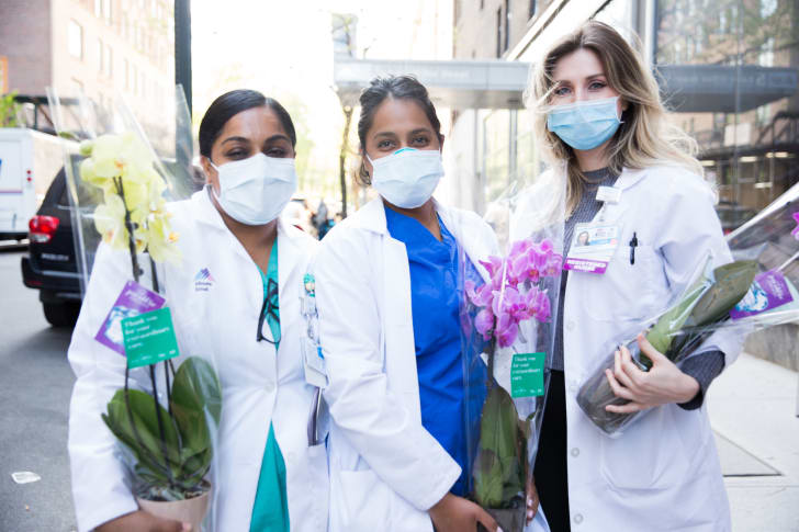 Healthcare workers hold orchids outside of a hospital
