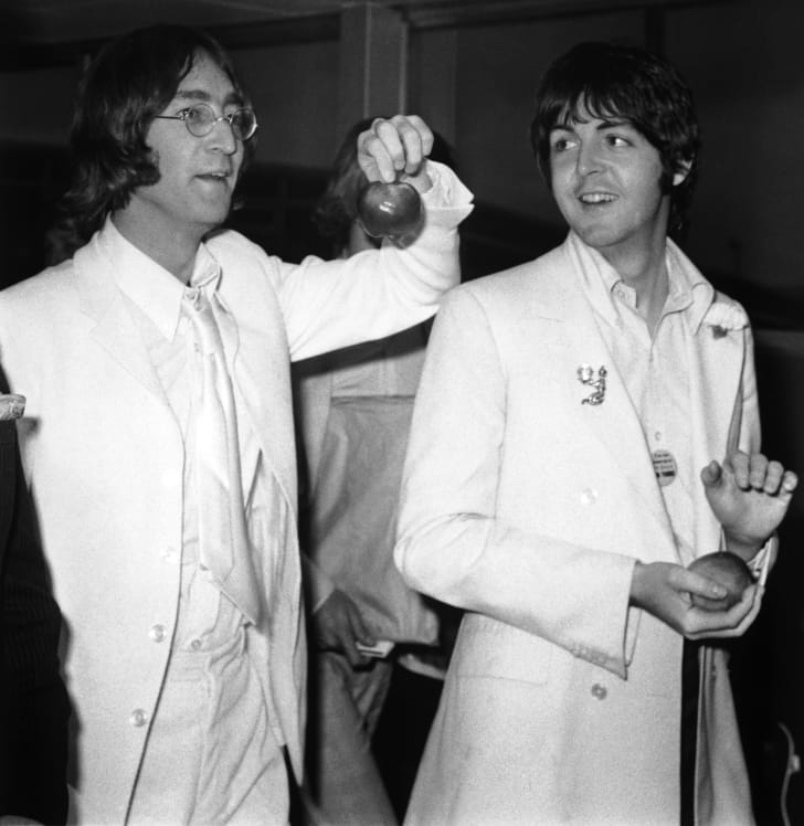 A photograph of John Lennon and Paul McCartney at London Airport in 1968.