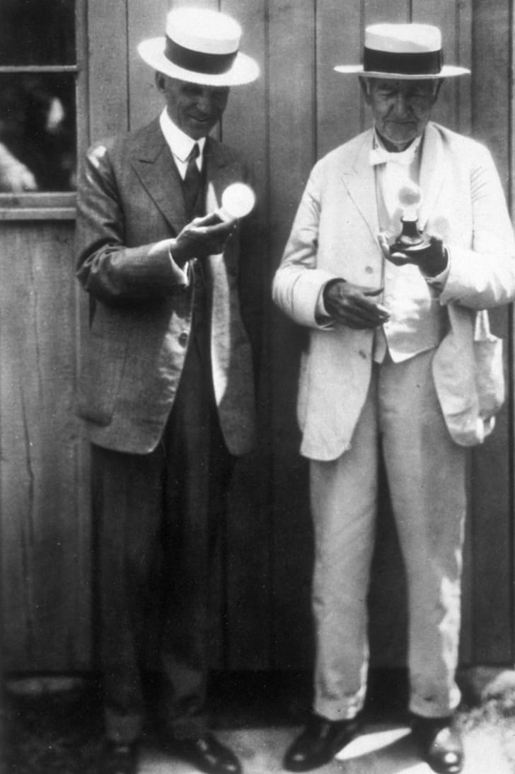 A photograph of Thomas Edison (right) and Henry Ford (left) examining Edison's incandescent lightbulb.