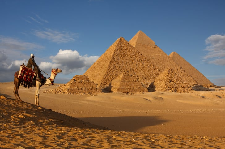 A man riding a camel near the Great Pyramids
