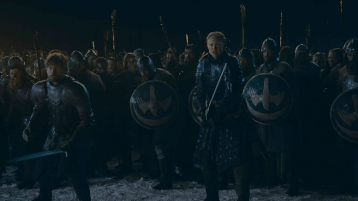 Nikolaj Coster-Waldau as Jaime Lannister and Gwendoline Christie as Bryenne of Tarth standing in front of soldiers with shields in Game of Thrones.