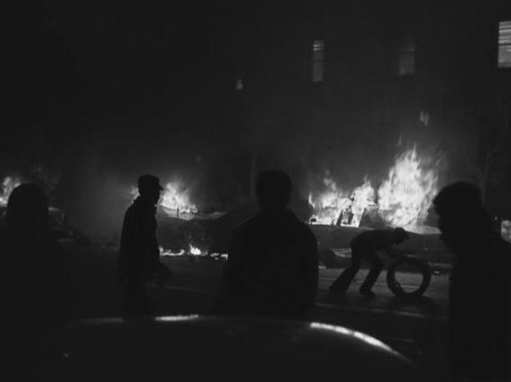 Rioters on the San Francisco Civic Center plaza causing property damage during the White Night riots. Burning police cruisers are in the background.