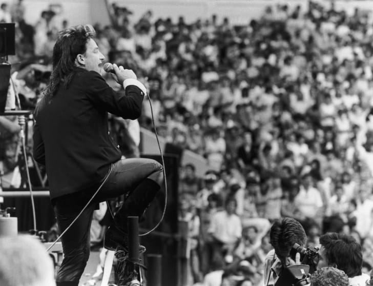A photograph of Bono performing with U2 at the Live Aid charity concert in London in 1985.