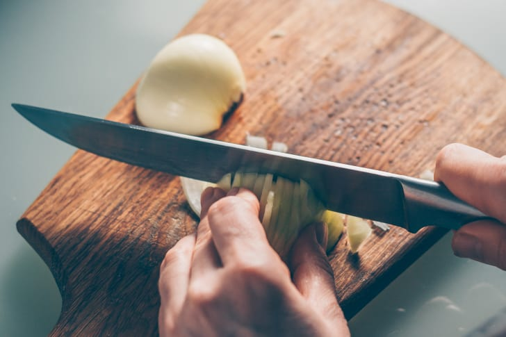 A person holding an onion by the root end and dicing an onion with a knife.
