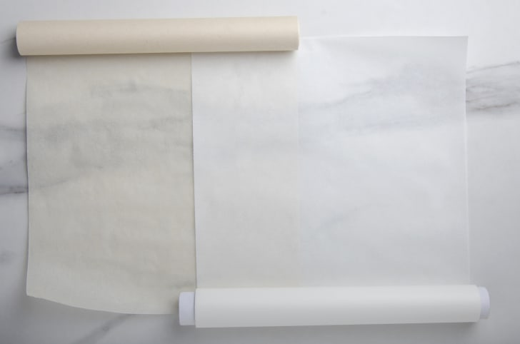 Two rolls of parchment paper on a white surface.