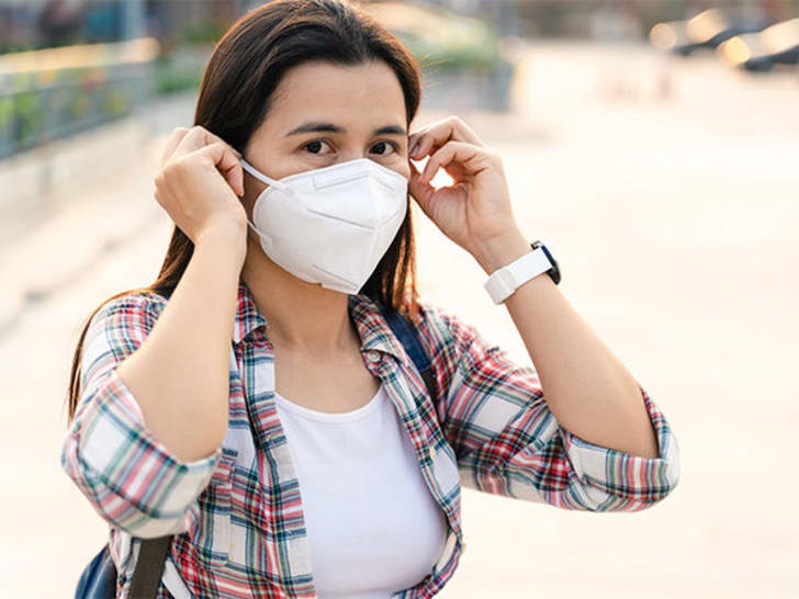 A woman putting on a protective mask.