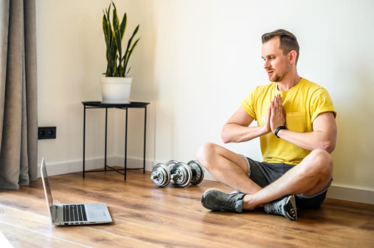 A man streaming a workout on a laptop.