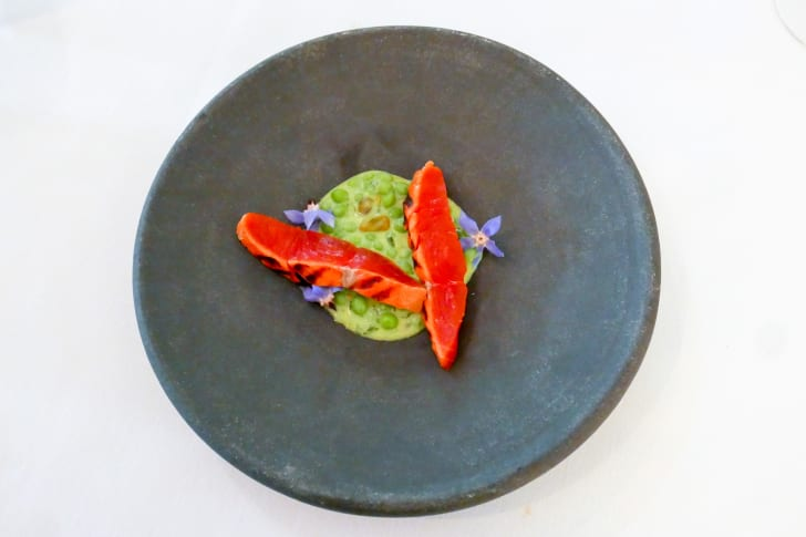 a small serving of salmon and peas on a gray plate