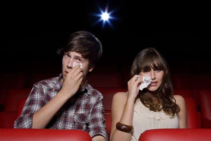 man and woman crying in movie theater