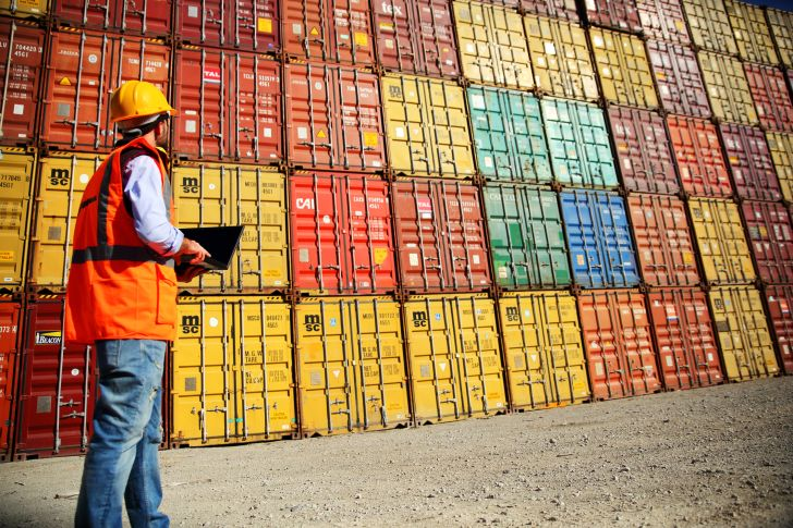 worker examining containers