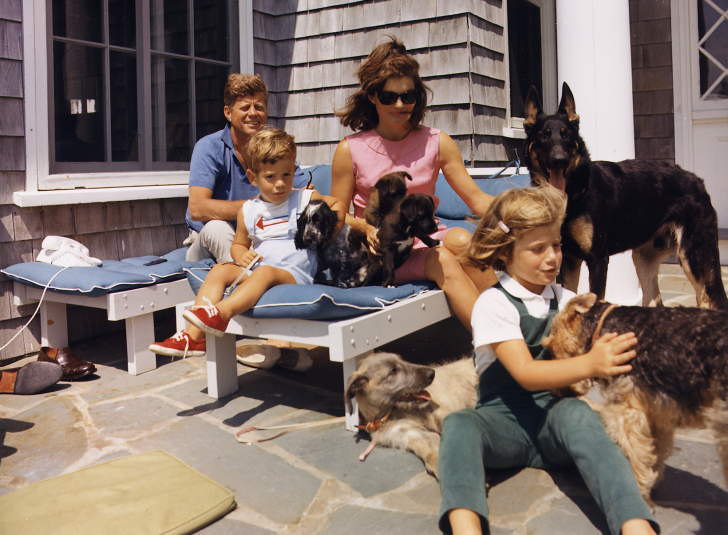 President Kennedy, John F. Kennedy Jr., Mrs. Kennedy, Caroline Kennedy. Dogs: Clipper ( standing ), Charlie ( with Caroline ), Wolf ( reclining ), Shannon ( with John Jr. ), two of Pushinka's puppies ( with Mrs. Kennedy ).