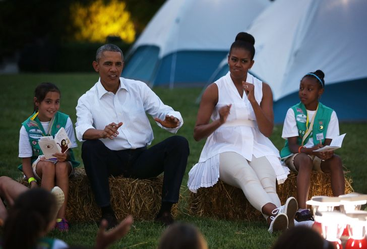 Barack and Michelle Obama camping with Girl Scouts.