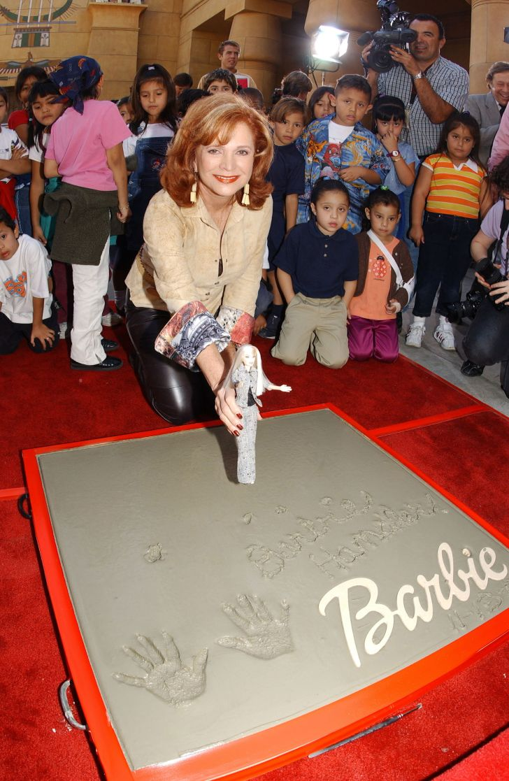 Barbara Handler, daughter of Ruth Handler and namesake inspiration for the Barbie doll, poses for a photograph after placing her hands in cement that will adorn the sidewalk at the Egyptian Theatre in Hollywood, California, in 2002.
