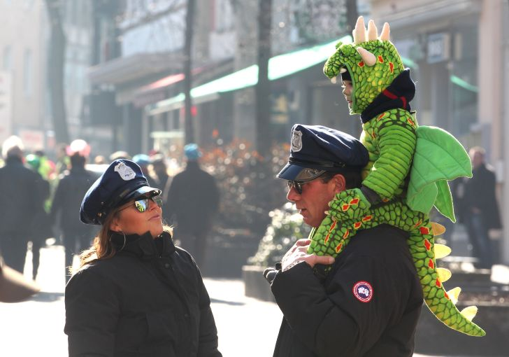 A child dressed as a dragon celebrates Ash Wednesday with his parents dressed as police officers in 2011.