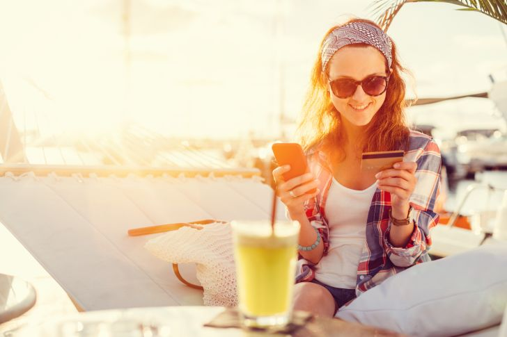 Woman whips out her credit card while hanging out on a hammock