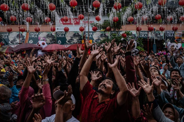 People crowd on the street during the Grebeg Sudiro festival in Solo City, Central Java, Indonesia. Grebeg Sudiro festival is held as a prelude to the Chinese New Year; people bring offerings known as gunungan.