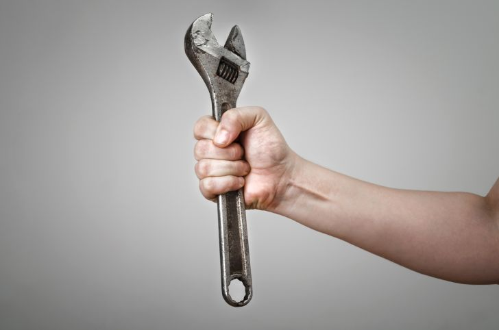 Person holding a metal wrench