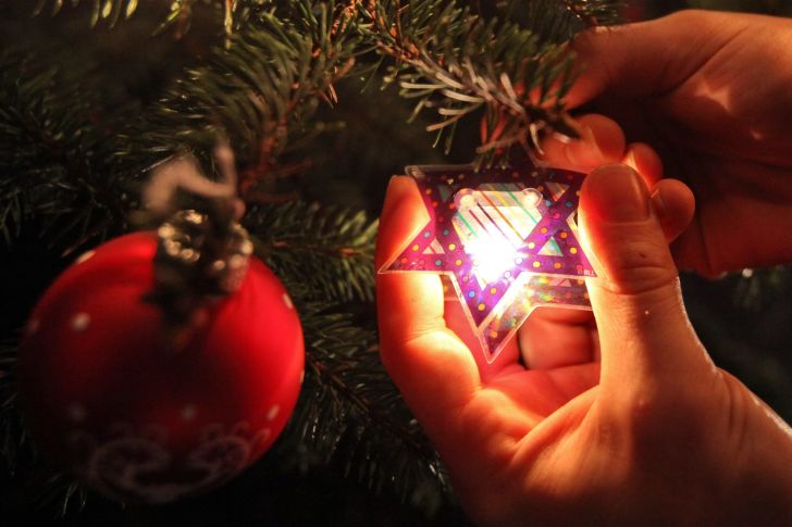Hanging a Star of David on a Christmas tree.