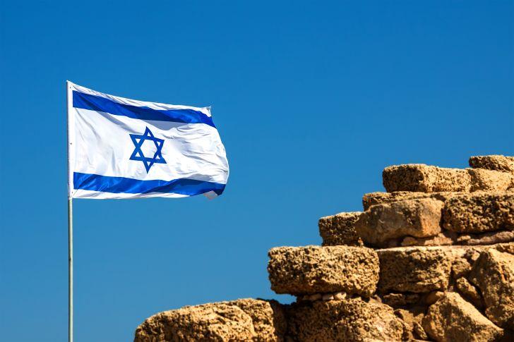 Israeli flag flying near a rock wall