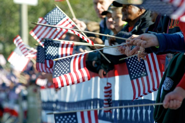 People holding American flags at Veterans Day Parade.