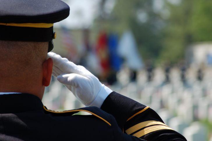 Soldier saluting in uniform in cemetery.