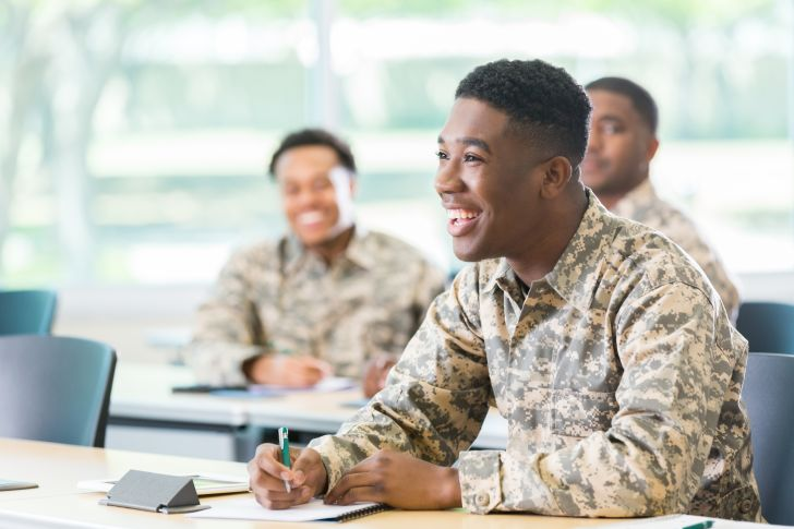 Military member laughing at a desk.