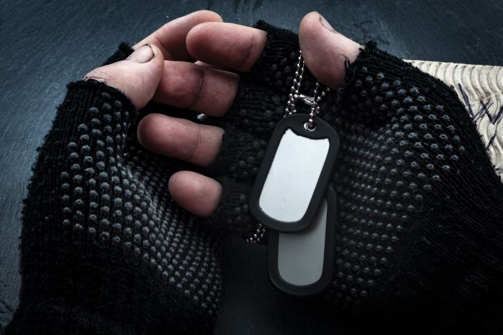 Hands with fingerless gloves holding military tags.