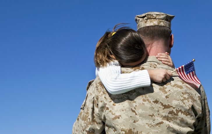 Young girl holding American flag embracing man in military uniform.