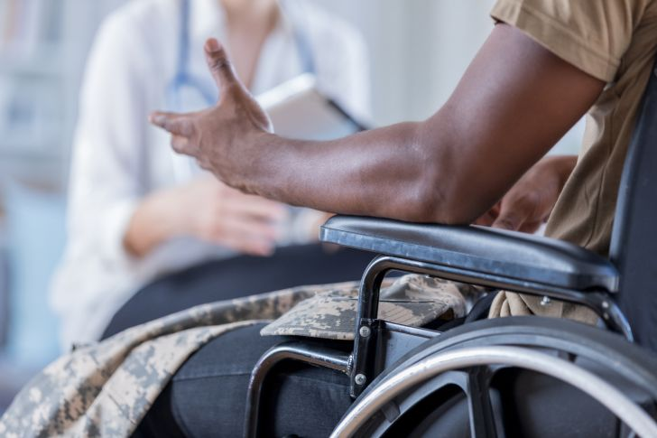 military man in wheelchair talking to doctor