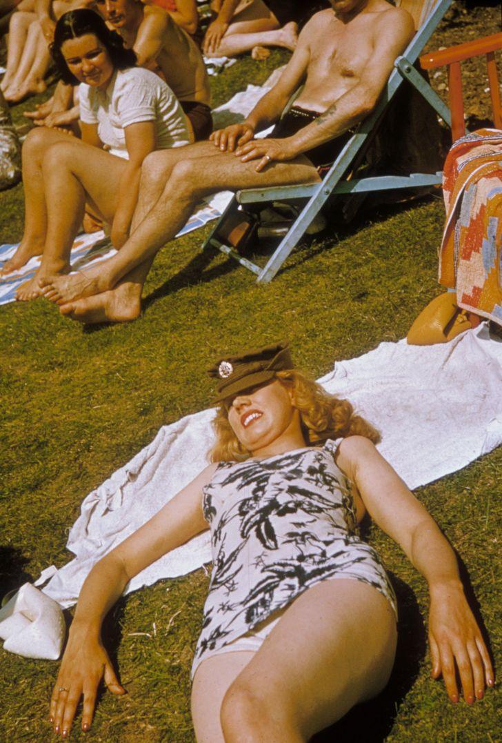 A British servicewoman sunbathing in her swimsuit and uniform cap, circa 1942.