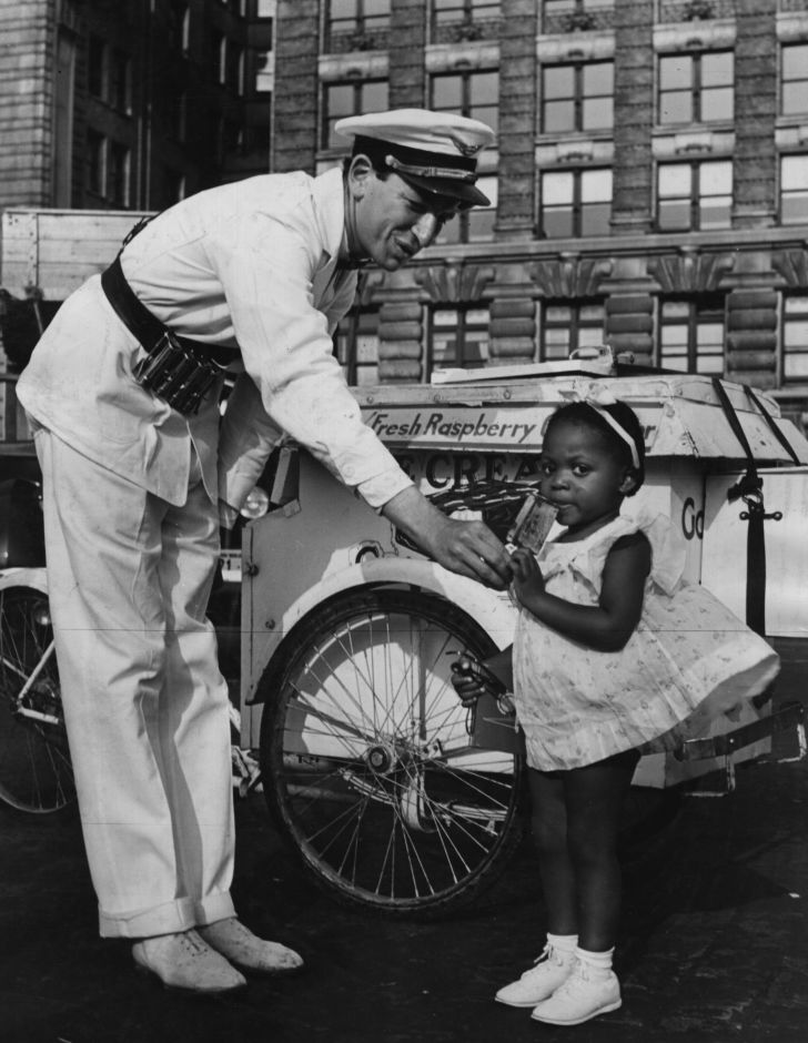An ice cream vendor in New York hands a young girl an ice cream in the 1920s.