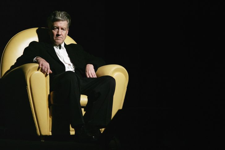 David Lynch seated in a large yellow chair.