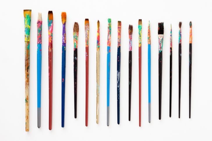 A bunch of dirty paint brushes on a white background.