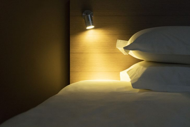 A light shining on a bed and two pillows.