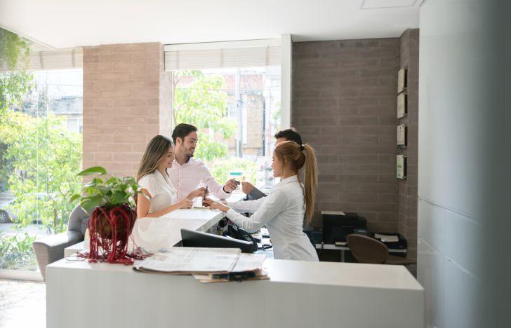 couples checks into hotel at reception desk