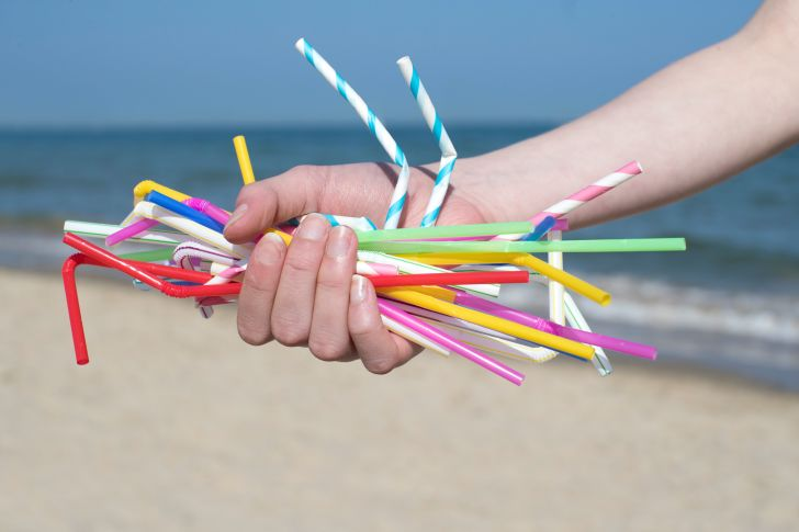 Someone grasping a handful of plastic straws