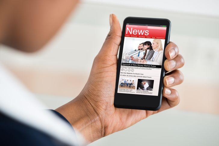 A person reading the news on their phone.