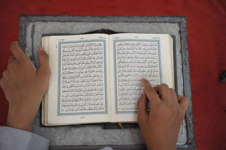 An Indian Muslim student recites from the Quran in a classroom during the holy month of Ramadan.