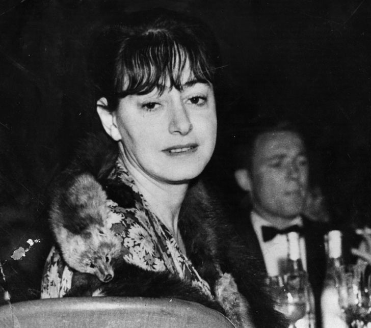 Dorothy Parker looks at the camera. There is a man in a tuxedo and wine bottles in the background.