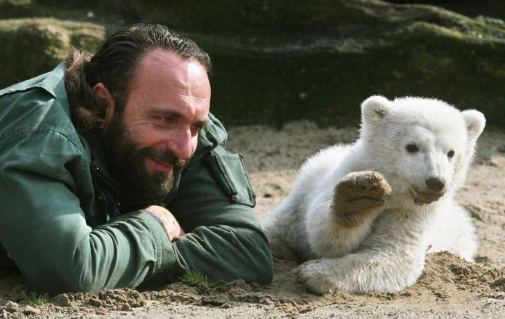 Knut and his handler pose for photos lying down on their bellies.