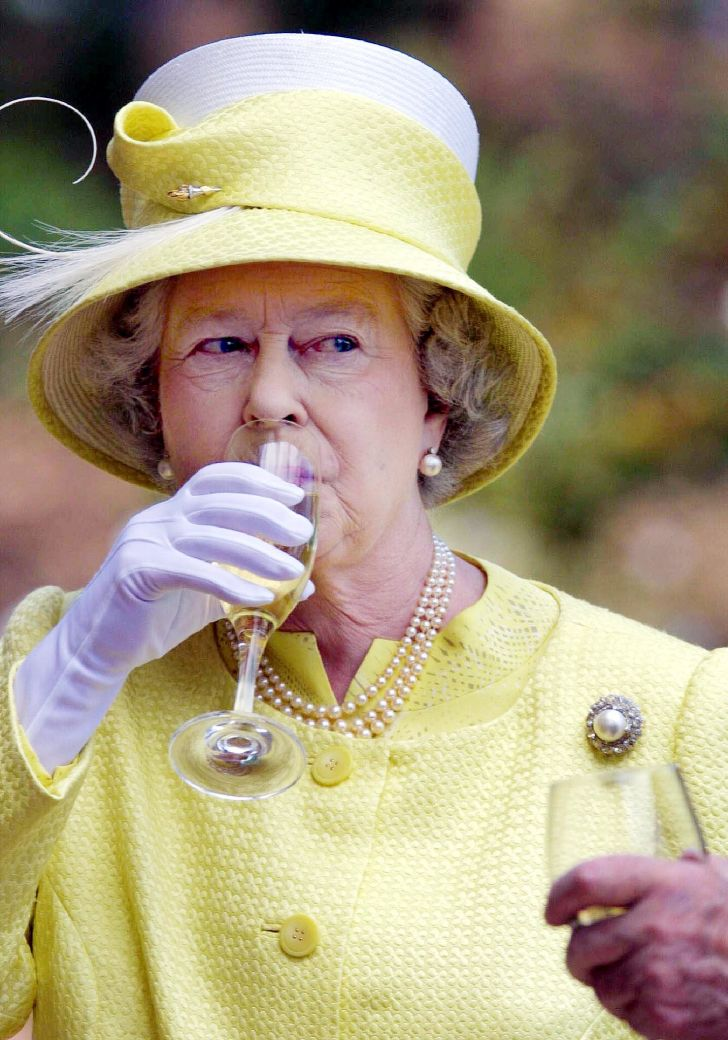 Queen Elizabeth II sipping a drink.
