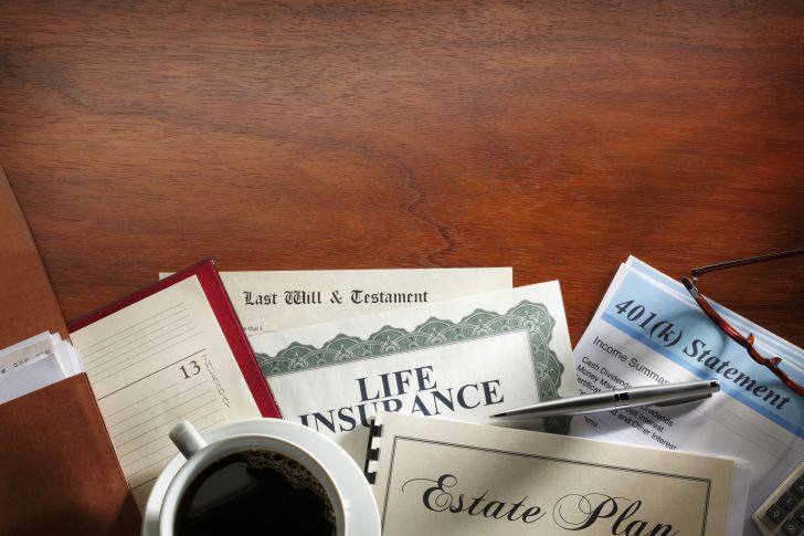 Important documents such as a life insurance policy, 401k statements, last will and testament, all fanned out on a wooden desk with a cup of coffee sitting next to them