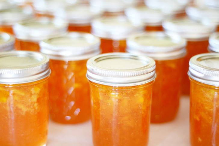 Offset rows of sealed glass canning jars filled with peach preserves