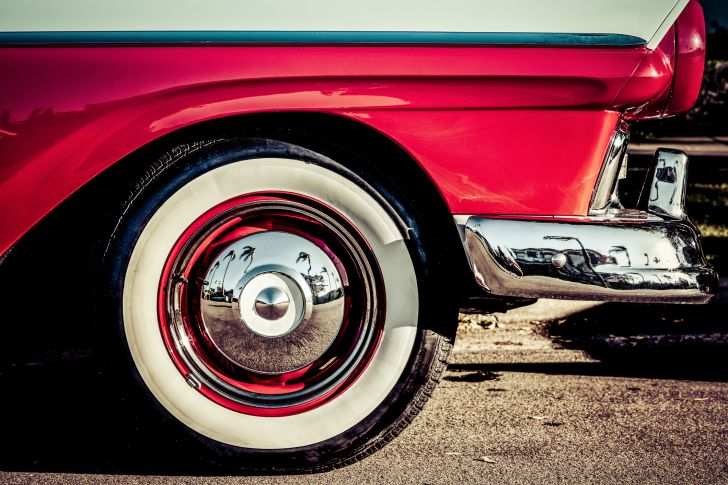 A hubcap of an old-fashioned red car with whitewall tires that show palm trees reflected in the hubcaps