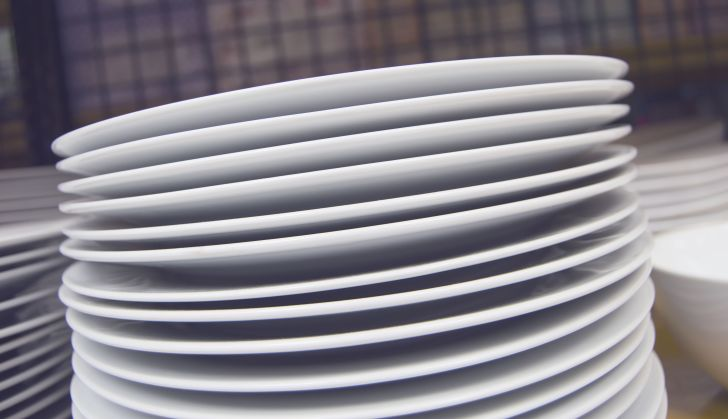 A stack of plain white dishes with a plaid background