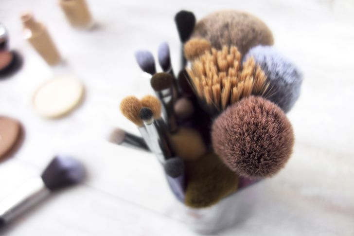 A cup full of makeup brushes of various shapes and sizes sitting on a white countertop.